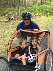 David Flanizig Standing next to his children in a Bicycle Ride-along  seat